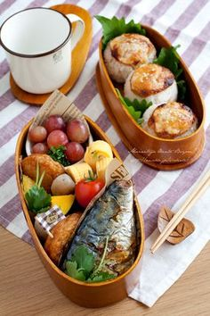 Grilled miso onigiri, tamagoyaki, squash, grapes, fish cakes, and what looks to be mackerel? Anyways, looks like a picnic/bent for two in our case.