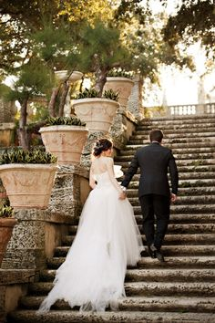 Lovely shot of the couple walking up a set of stone stairs.