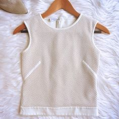 Akris sleeveless top Known for is Swiss dots...you will not be let down in this Akris Punto sleeveless perforated top. Zippered back. Banded bottom. Just a hint of design elements on the side keeps this relevant and fresh. Front is ully lined in a nude sheer. Cotton/poly/viscose/nylon blend has a bit of stretch while keeping the structure Akris is known for. Excellent condition .No size tag..fits like a small ..15.5 pit to pit, 14 shoulder, 11.5 pit to hem. NO PPNO OFFERSPRICE FIRM I ONLY…
