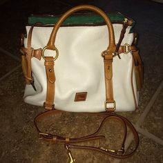 """Dooney and Bourke cream/ivory satchel handbag. Used one time. In dust bag ever since. I got as a gift, just not my style. It has marks from the handle while being stored. I did not try getting it off.  (look in pic) Leather cleaner may take it right off.  All measurements approximate 11"""" across (zipper area) 11"""" length bottom 6""""'wide (bucket part). Inside looks and smells brand new!! This was 400$ brand new. (I looked it up when I received it). I will keep if I don't get close offer. 😊…"""
