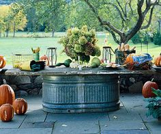 A horse trough topped with an old door stands in as a buffet table. This reminds me of our days going to Wimberley- swimming in a horse trough and eating off of an outdoor spool table. Horse Trough, Cattle Trough, Cow Trough, Fall Harvest Party, Water Trough, Metal Trough, Metal Tub, Outdoor Projects, Outdoor Ideas