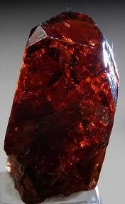 Jacinth is a red variety of zircon (zirconium/silicon/hafnium)  found in magmatic, metamorphic, pegma-titic, alluvial rocks. Zircons are commonly slightly radioactive due to trace amounts of uranium & make prime, geochronology age indicators