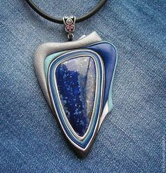 Купить или заказать Кулон из кожи 'Лунная дорожка' в интернет-магазине на Ярмарке Мастеров. Кулон из кожи с лазуритом. Камень синего цвета с вкраплениями пирита (искрится серебром), поэтому работа названа 'Лунная дорожка'. Кажется, что по камню с одной стороны разбросаны серебристые чашуйки. Основной цвет кожи серо-голубой металик, синий, голубой, с белой отделкой. Считалось, что лазурит может очистить ауру человека от любого негатива, снять ощущения тревоги, избавить от тяжёлых…