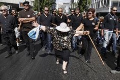 FRONT AND CENTER: An elderly woman protested in Athens Monday. Hundreds of striking city workers marched through the streets to protest publ...