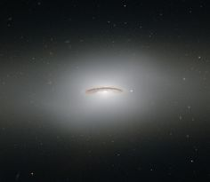 This neat little galaxy is known as NGC 4526. Its dark lanes of dust and bright diffuse glow make the galaxy appear to hang like a halo in the emptiness of space in this image from the NASA/ESA Hubble Space Telescope.
