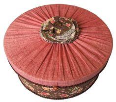 6. Caixa Patchwork redonda, rosa com marrom. Área Interna: LxCxA = 25 x 25 x 10. Preço: R$65,00.
