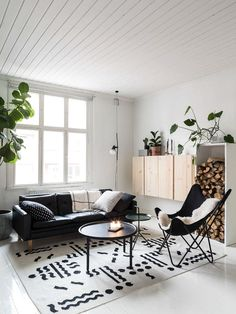 Living room with white panelled ceiling, wood box, and leather couch.