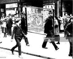 Anti-German riots in Poplar, London. Police carrying wire netting in a wooden frame for protecting shop windows. Photograph. 1914-1918.