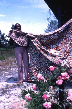 """Queen Udell has patience 'just like Job,' according to her husband. The 57 year old woman learned to make yo-yo quilts from her mother and grandmother. These yo-yos are sewn up with embroidery thread, flattened and sewn together by hand. Ms. Udell estimates there are approximately four thousand of the dime-sized yo-yos in this quilt, which took over a year to complete... 'People give me scraps and I just sews'um.'"" (photo 1979)"