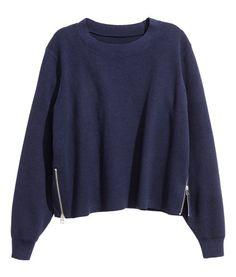 Mörk blåmelerad. En kort, finstickad tröja i stadig, bomullsblandad kvalitet. Tröjan är ribbstickad runt krage och vid ärmslut. Rak passform. Dragkedja i