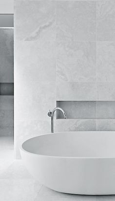 all surfaces the same stone, floating soaking tub, use of alcove for accessories at tub wall