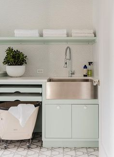 Contemporary laundry room feature stacked pull out drying rack in pale green cabinetry with white pulls while a stainless steel apron sink brings a vintage vibe along with a pullout faucet. Vintage rolling laundry hamper is tucked under the cabinetry complimenting the style and adding a functional and practical use of space.
