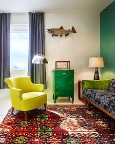 Yellow chair, floral black couch, green pillow, green wall, fish wall art, grey curtains, and red printed rug