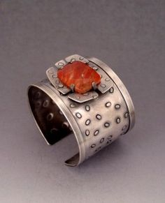 Handmade sterling silver wide cuff bracelet with a turtle set orange calcite cabochon. cuff band textured with hand stamped small ovals.