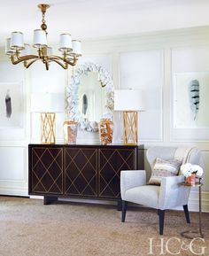 In the entry, lamps from La Luz sit atop an ebonized-walnut credenza. The mirror is from Made Goods, the Aerin chandelier is from Visual Comfort, and the vases and chair are from English Country Antiques.