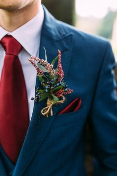 A classic blue three piece suit with dark red tie and pocket square sets off this magnificent buttonhole by @whfco. Photo by Benjamin Stuart Photography