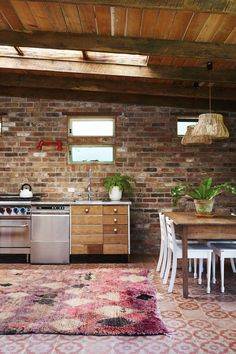 A rustic kitchen with exposed brick and Jatana tiles with a soft vintage Moroccan boujad rug. 'Star Eyes' boujad rug available from http://tigmitrading.com/collections/rugs/products/star-eyes-boujad