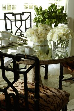 Beautiful Dining room! Love the Mirrored Table &  Black lacquered chairs. The flowers are the finishing touch! Designed by Andrew Raquet