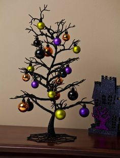 Amazon.com - Spooky Tree with Ornaments Table Decor. I think my Nightmare Before Christmas Photos would be fun on this.