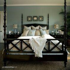 Master bedroom with aqua walls, dark wood bed, cream spread, and shells