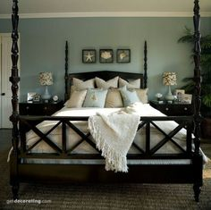Master bedroom with aqua walls, dark wood bed, cream spread, and shells