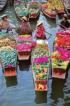 market traders in boats laden with fruit + flowers // bangkok, thailand