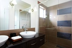 Bathroom I designed recently for a builder's display home using a semi-frameless shower screen and coffee and black tiles. (C) Ethos Design.