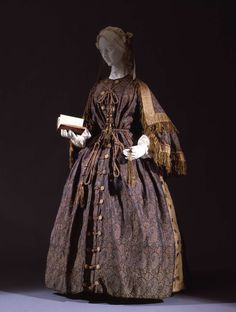 Ca.1860 paisley wool princess-cut wrapper with chenille-fringed open sleeves and matching capelet. Hazel-colored silk insets at side of skirt; open front with frogged button closure; drawstring waist; original cord belt. Galleria del Costume di Palazzo Pitti, Italy.