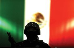 A Mexican federal policeman stands before his nation's flag. (Photo by Jesús Villaseca Pérez.)