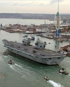 Britain's largest ever warship arrived at her home base of Portsmouth for the first time this morning after almost two months of sea trials to be greeted by Theresa May.  HMS Queen Elizabeth, a £3 billion aircraft carrier, steered into the harbour towed by tug boats at just after 7am. Family members of the 700-strong crew waited on the jetty from dawn to greet the sailors as the warship towered into view.