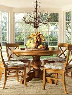A round dining table with a bountiful centerpiece.