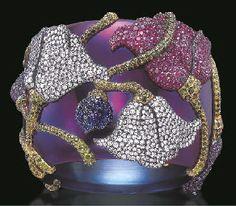 A MAGNIFICENT MOGOL FLOWER BANGLE BRACELET, BY JAR; coloured sapphires and diamonds in blackened silver and gold.
