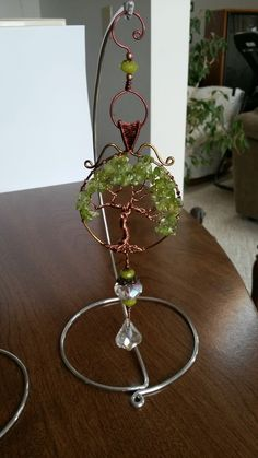 Wire wrapped tree of life sun catcher with peridot chips and beads with display stand out of aluminum wire.