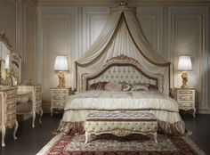 Luxury classic style bed for Louvre 943 bedroom made by Italian craftsmen in the style Louis XV. This classic style bed is distinguished by the beauty of its capitonné headboard as same on the beautiful bench at its feet. The headboard of the  classic style bed is decorated by beautiful frame in pink pleated fabric and floral carvings with golden finish on the top of the bed. Also note the beautiful wall canopy, perfect complement to an important classic style bed, and nightstands nicely…