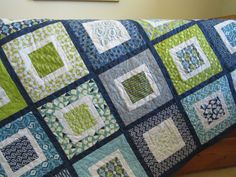 "This is a wonderful geometric quilt to display in your home. The colors in this quilt are mainly blue, aqua, gray and green. This quilt would be a wonderful gift. This handmade quilt is 58"" wide by 69"