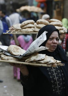 A women balancing a tray of bread On his shoulder, which she has just bought from a bakery in Cairo , Feb. 6, 2008. that sells government-subsidized bread. A change in the subsidy system by the Egyptian government has led to bread shortages, rising prices and long lines outside of bakeries selling the far-cheaper subsidized bread. REUTERS/Nasser Nuri (EGYPT)