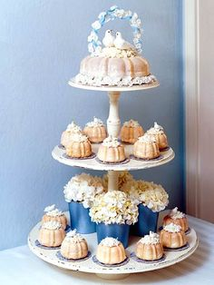Miniature Cakes:   This might be a perfect cake for a small wedding, engagement party, or bridal shower. Miniature bundt cakes encased in a vanilla glaze are set on the bottom levels. The top tier is a larger cake and wedding topper of doves. Set extra cakes on silver trays to accommodate a larger guest list.