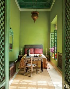 The Green Bedroom, a guest room in a Marrakech riad, is appointed with a 19th-century Persian light and a bone-inlay-embellished desk and chair.
