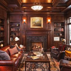 Library with the deep colored wood walls and stone fireplace. The leather couch and rug are perfect, too. Needs more bookshelves, though. I like the window though for natural light. A sky light would be even better.