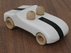 Two passengers in a white stylish car. Dimensions: about 15 cm long, 7 cm wide, 5.5 cm high (approximately 6 x 2.5 x 2.25). The look of the product