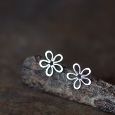Dainty minimalist wild flower stud earrings made from solid sterling silver wire. Each petal outline is carefully bent into shape by hand and gently hammered - this adds a subtly organic look to the f