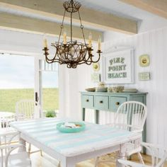 Love the painted table, white chairs and side board.