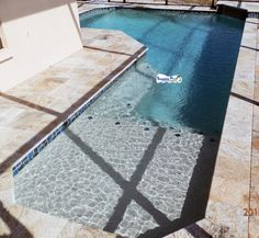 Superior Pools Port Charlotte FL www.superiorpoolsswfl.net   7 shape pool with travertine coping and pavers with a sun shelf