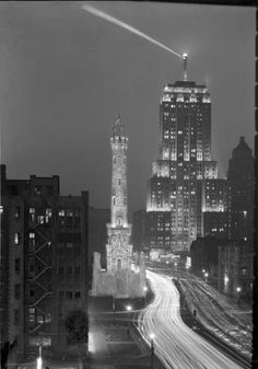 Night view of the Palmolive Building with the Water Tower in the foreground. The lights are from automobiles creating movement streaks on Michigan Ave., c. 1931. Photograph by Ken Hedrich.