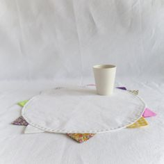 Round place mat in white linen with colorful edges.