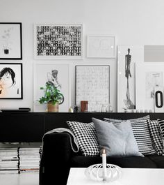 Black and white living room with lovely wall art. How good looking is that black sofa?