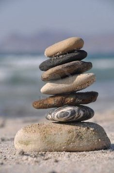 Picture of beautiful pebble stack on a sandy beach (sea on the background) stock photo, images and stock photography. Foto Website, Stone Balancing, Stone Cairns, Miramar Beach, Beach Stones, Am Meer, Pebble Art, Pebble Stone, Stone Art