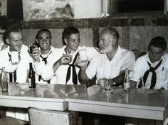 Ernest Hemingway at a bar in Cuba (I think it's the Bodeguita del Medio, which makes his fave mojito) with a bunch of sailors.