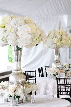 Centerpieces White tall centerpieces lush mercury glass orchids hydrangeas roses dusty miller floral chiavari chairs reception lace table linen tent Outdoor hydrangea centerpieces