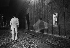 #1967. Sublime photo des adieux de Jacques #Brel à la scène. Cela fait 15 ans que Brel chante et il a décidé d'arrêter. Après avoir fait son dernier #Olympia où on lui a fait la plus folle ovation de l'histoire de ce lieu mythique il s'en va comme ici chanter une dernière fois à #Roubaix. Après son tour de chant il s'en va marche sur les pavés mouillés et passe devant une de ses affiches sans même la regarder. Photo : Andre Lefevre / @parismatch_magazine by parismatch_vintage
